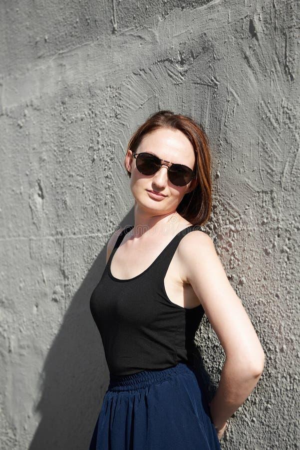 Młoda dziewczyna pozuje przeciw betonowej ścianie, ubierającej w czerni, har obrazy stock