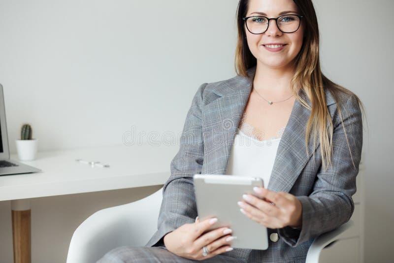 Młoda dziewczyna pracuje w biurze przy stołem zdjęcia royalty free