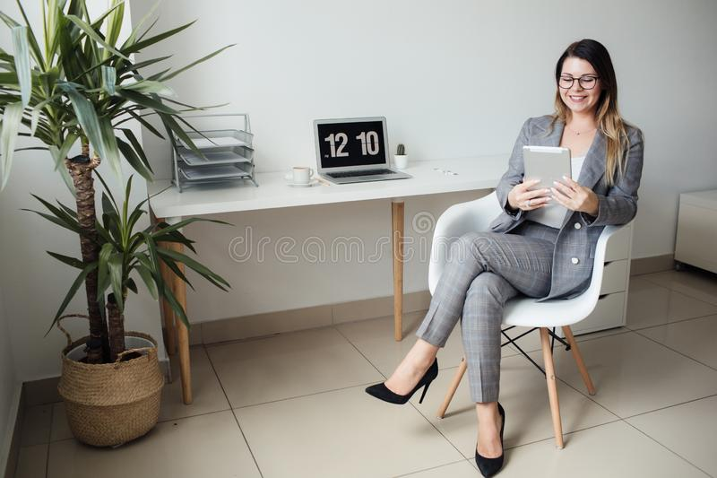 Młoda dziewczyna pracuje w biurze przy stołem zdjęcie stock