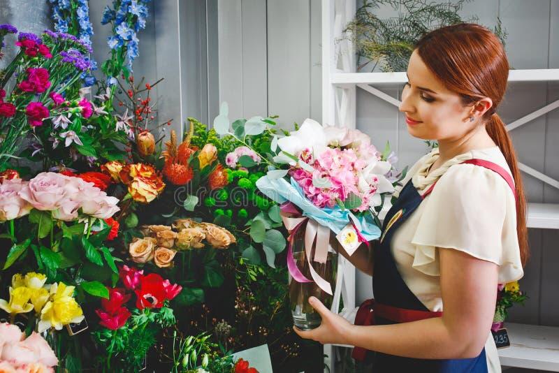 Młoda dziewczyna pracuje w kwiatu sklepie zdjęcia royalty free