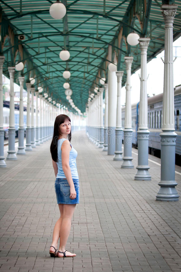 Młoda dziewczyna przy dworcem blisko błękitnego pociągu zdjęcie royalty free