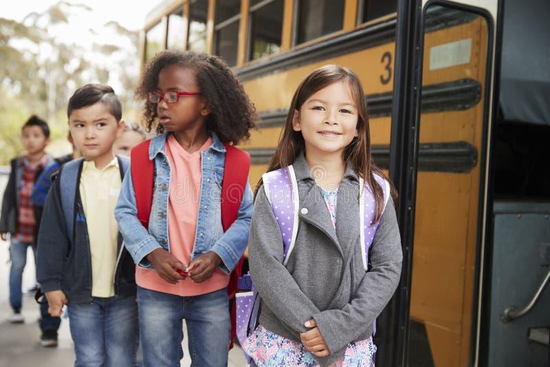 Młoda dziewczyna przy głową kolejka dla autobusu szkolnego obrazy royalty free