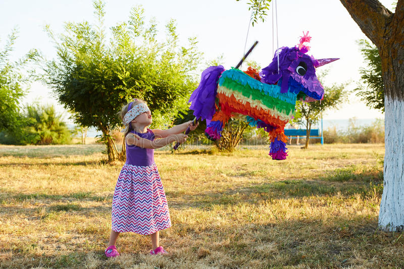 Młoda dziewczyna przy plenerowym przyjęciem uderza pinata zdjęcie royalty free