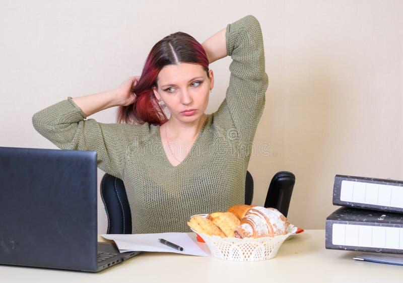 Młoda dziewczyna przy stołem w biurze prostuje włosy, patrzeje w komputer obrazy royalty free