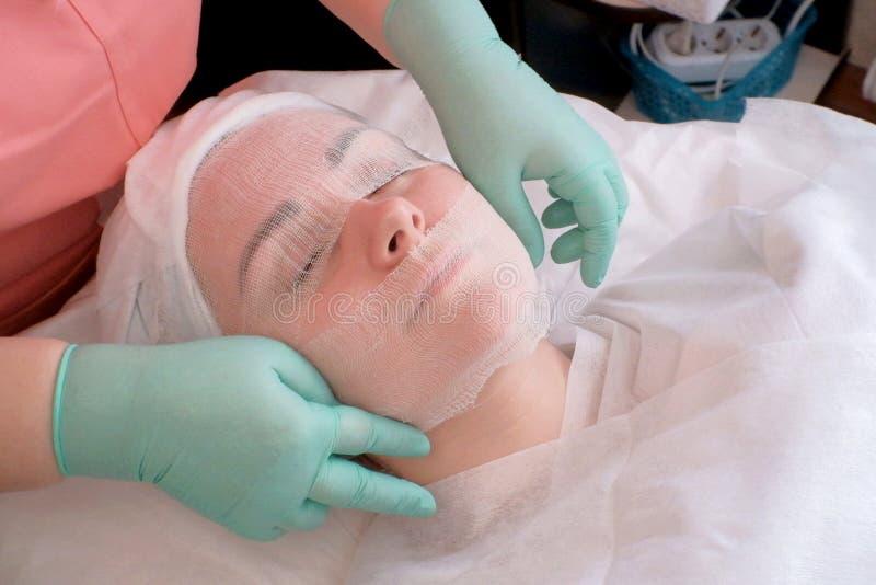 Młoda dziewczyna relaksuje w piękno salonie Beautician zakrywa gazy kobiety twarz Przygotowanie dla kosmetycznych procedur obraz royalty free