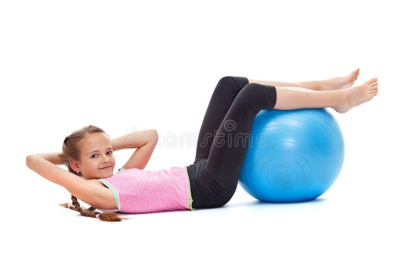 Młoda dziewczyna robić siedzi podnosi z wielką gimnastyczną piłką obrazy stock