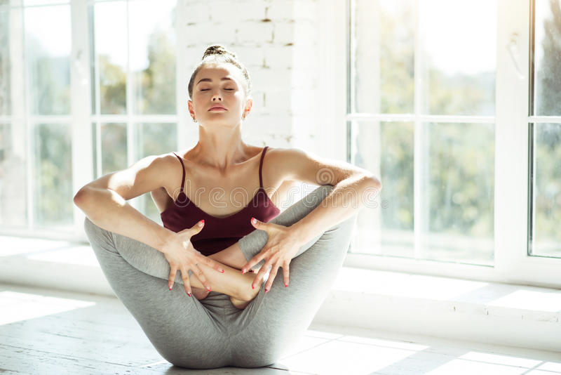 Młoda dziewczyna robi joga ćwiczeniom zdjęcia stock