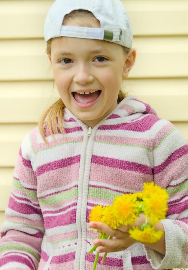 Młoda dziewczyna robi wiankowi żółci kwiaty dandelion fotografia stock