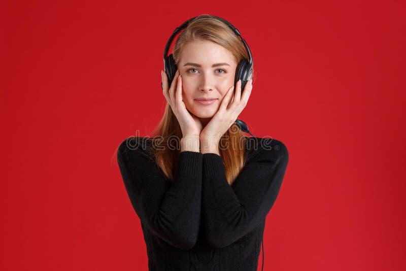 Młoda dziewczyna słucha muzyka w hełmofonach i ono uśmiecha się łatwo, Na czerwonym tle obraz royalty free
