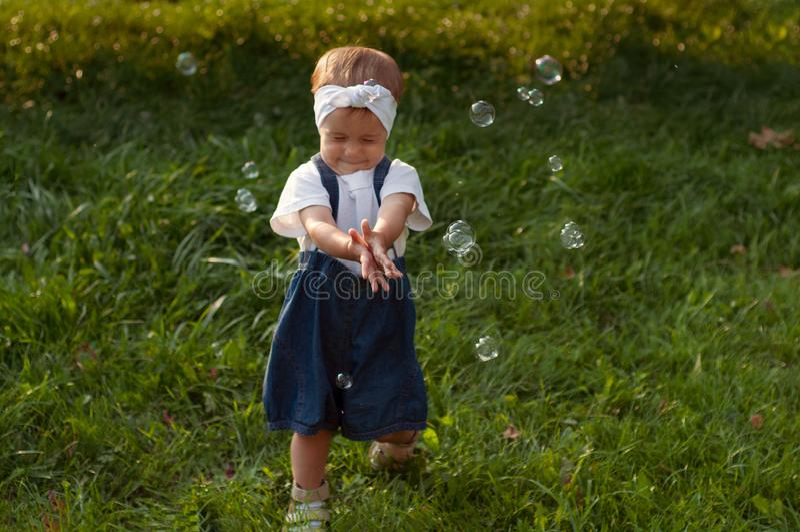 Młoda dziewczyna siedząca na trawie bawiąca się bąbelkami obrazy stock
