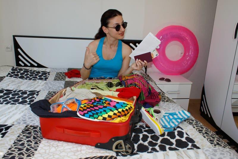 Młoda dziewczyna siedzi blisko walizki Dziewczyna obok overfilled walizki Dostawać przygotowywający dla podróżować zdjęcie royalty free