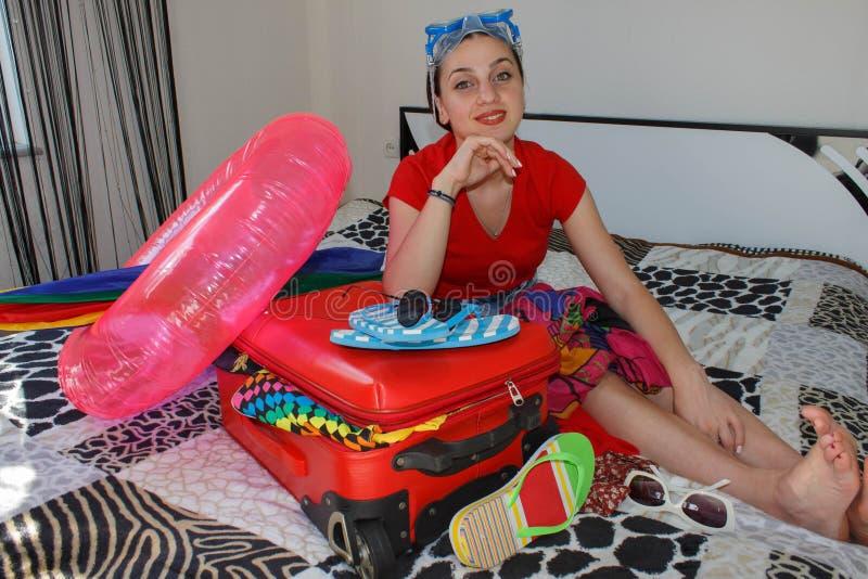 Młoda dziewczyna siedzi blisko walizki Dziewczyna obok overfilled walizki Dostawać przygotowywający dla podróżować obrazy royalty free