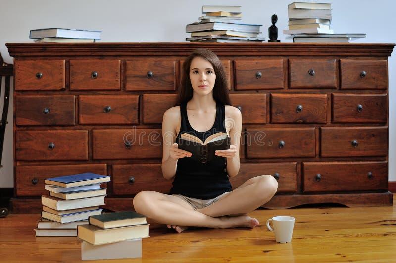 Młoda dziewczyna siedzi na podłoga wśród książek z ope zdjęcie stock