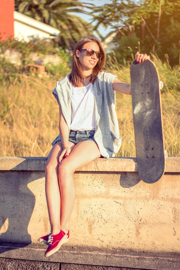 Młoda dziewczyna siedzi nad ścianą z deskorolka obrazy stock