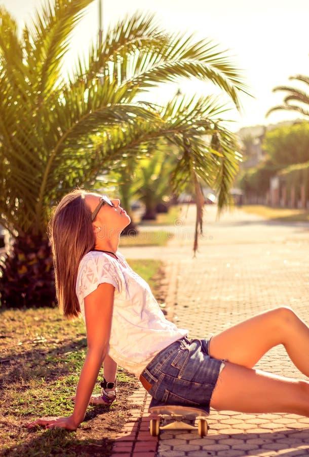 Młoda dziewczyna siedzi outdoors dalej z deskorolka obrazy stock