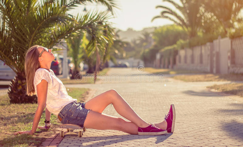Młoda dziewczyna siedzi outdoors dalej z deskorolka zdjęcia royalty free