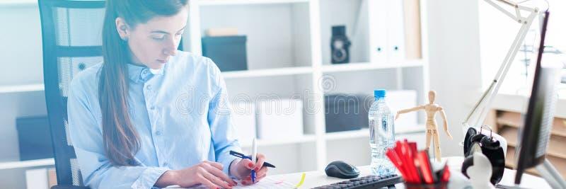 Młoda dziewczyna siedzi przy stołem w biurze, trzyma pióro w jej ręce i działanie z dokumentacją zdjęcia stock