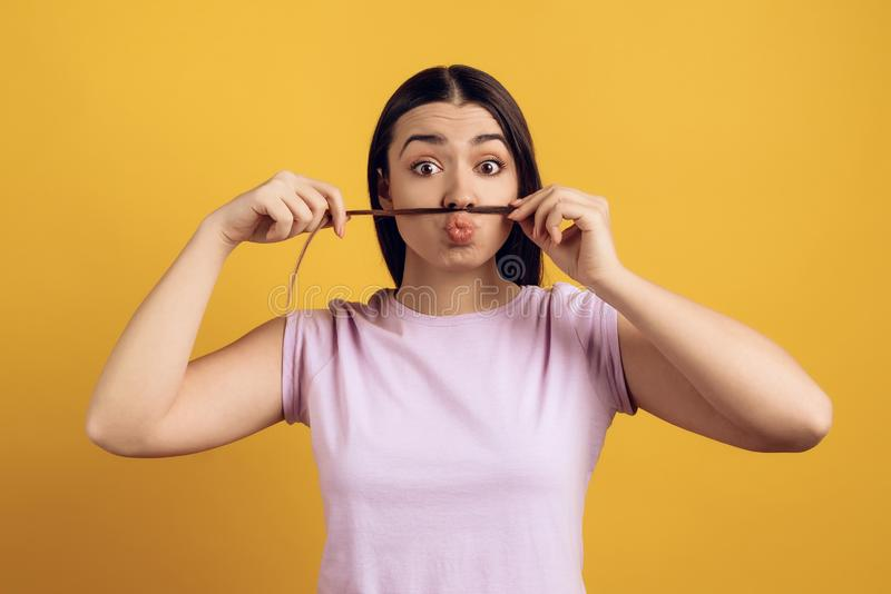Młoda dziewczyna stawia pasemko włosy pod nosem zdjęcia royalty free