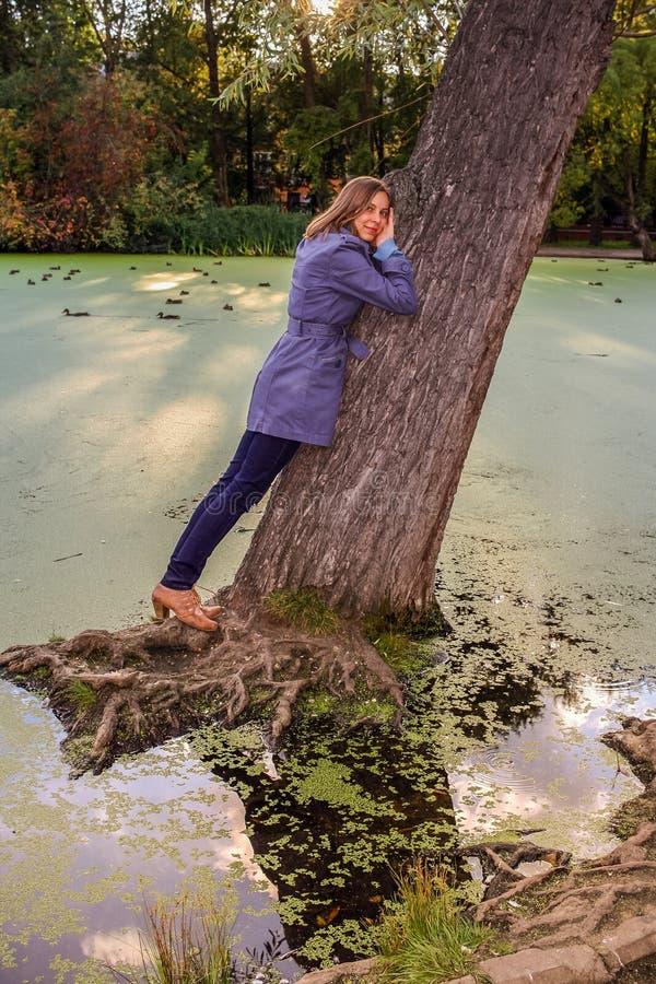 Młoda dziewczyna stoi opierać przeciw wielkiemu chylenie puszka drzewu w wodzie w jesieni obraz royalty free
