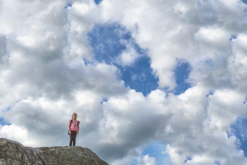 Młoda dziewczyna stojaki na skale przeciw tłu niebo fotografia stock
