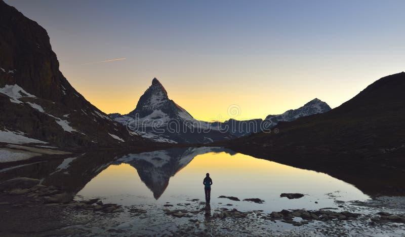 Młoda dziewczyna stojaki przed jeziorem dokąd Matterhorn 4478m i Dente Blanche 4357m odbijaliśmy w Riffelsee fotografia stock