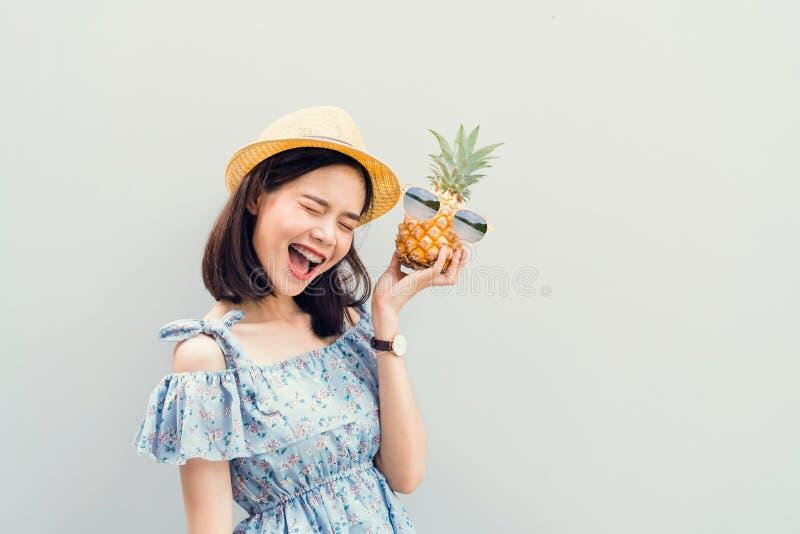 Młoda dziewczyna szczęśliwy uśmiech, rozochocony w błękit sukni i, trzymamy dwa ananasa w ręce obrazy royalty free