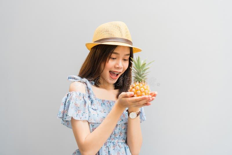 Młoda dziewczyna szczęśliwy uśmiech, rozochocony w błękit sukni i, trzymamy dwa ananasa w ręce fotografia royalty free