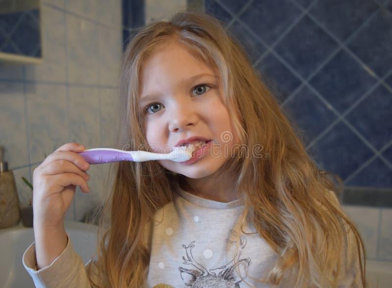 Młoda dziewczyna szczotkuje zęby przed dziecinem obrazy royalty free