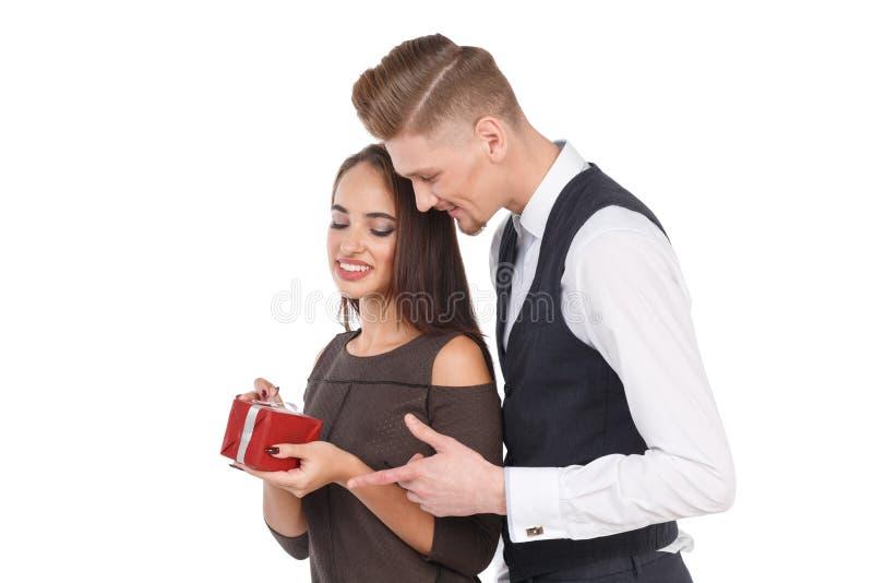 Młoda dziewczyna trzyma prezenta pudełko facet ściska dziewczyny od behind odosobniony obrazy royalty free