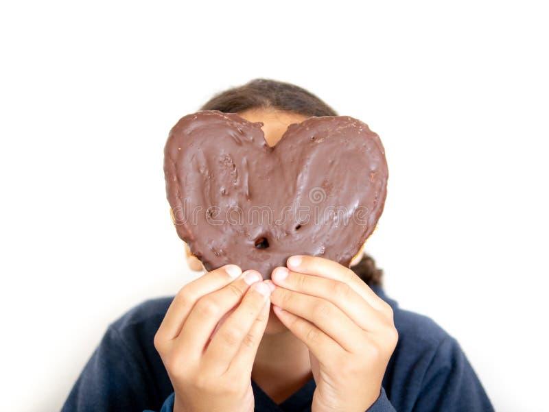 Młoda dziewczyna trzyma sercowatego ptysiowego ciasto zdjęcia stock