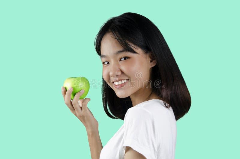 Młoda dziewczyna trzyma zielonego jabłka z białym tłem obrazy stock
