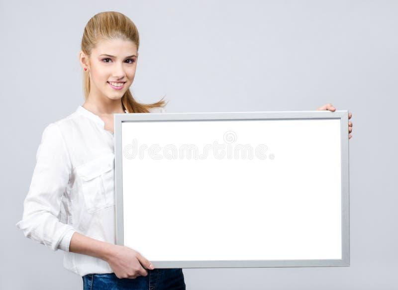 Młoda dziewczyna uśmiecha się białą puste miejsce deskę i trzyma obrazy royalty free