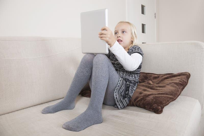 Młoda dziewczyna używa pastylka peceta na kanapie obrazy stock