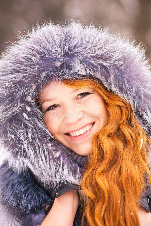 Młoda dziewczyna ubierał w futerkowym żakiecie przy zim drzew tłem obrazy stock