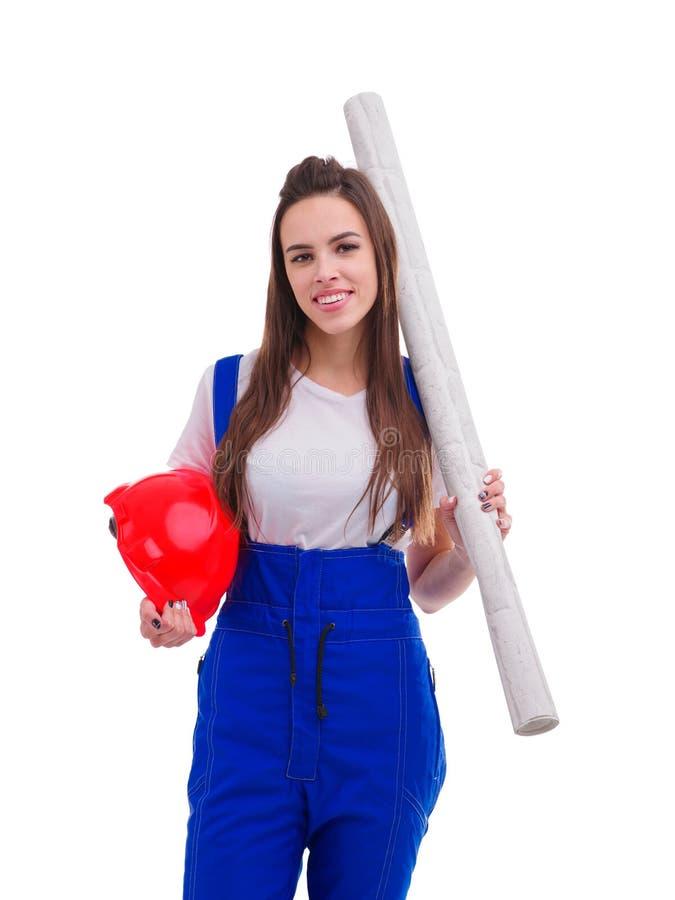 Młoda dziewczyna, ubierająca w mundurze, stoi rolkę tapeta na ramieniu i trzyma hełm i odosobniony fotografia royalty free