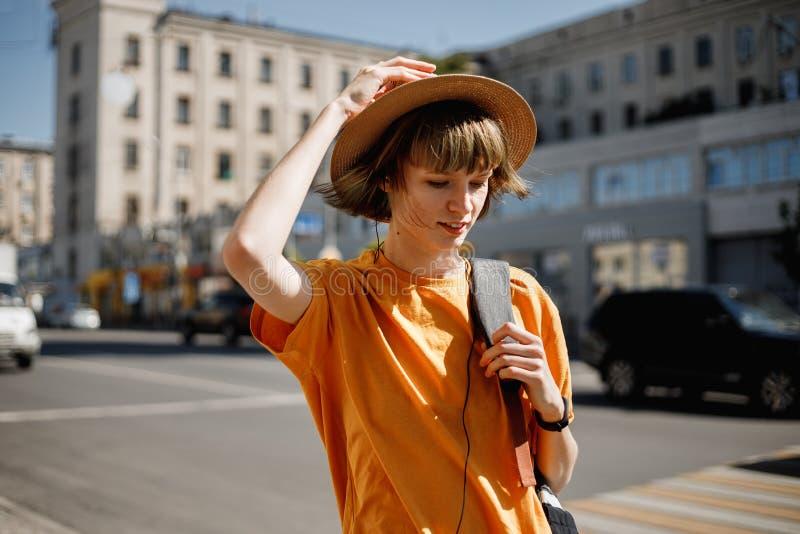 Młoda dziewczyna w żółtej koszulce słomianym kapeluszu i chodzi z plecakiem wzdłuż miasto ulicy na lato słonecznym dniu zdjęcia royalty free