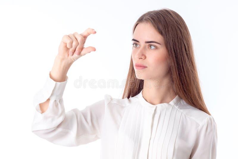 Młoda dziewczyna w białej koszula podnosił jeden rękę up z przegiętymi palcami odizolowywającymi na tle obraz stock