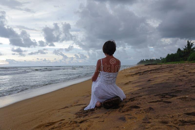 Młoda dziewczyna w białej sukni spotyka zmierzch na plaży tropikalny ocean zdjęcia royalty free