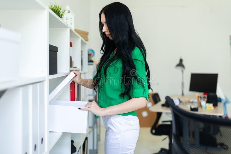 Młoda dziewczyna w biurze bierze out białego pudełko obrazy royalty free