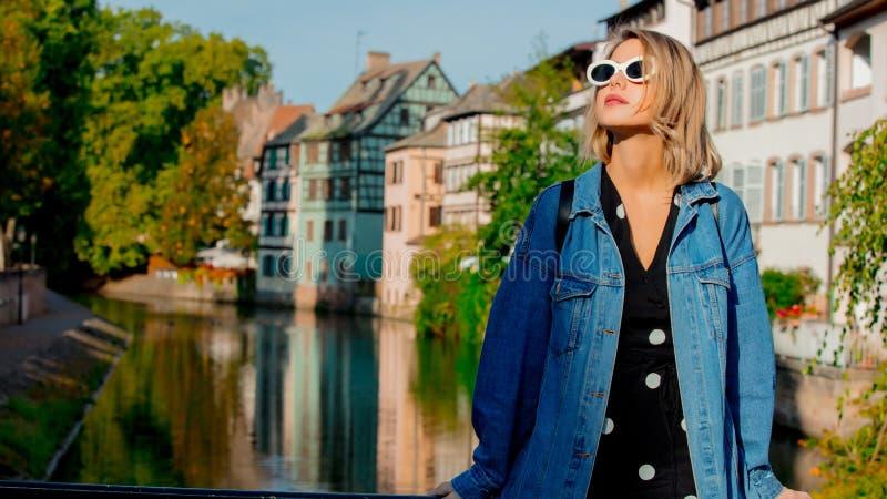 Młoda dziewczyna w cajgach kurtka i okulary przeciwsłoneczni na ulicie Strasburg obrazy royalty free
