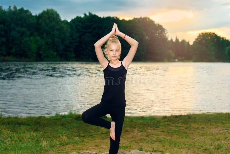 Młoda dziewczyna w czarnych leggings i koszulce siedzi na kamieniu w lotosowej pozie blisko jeziora zdjęcia stock