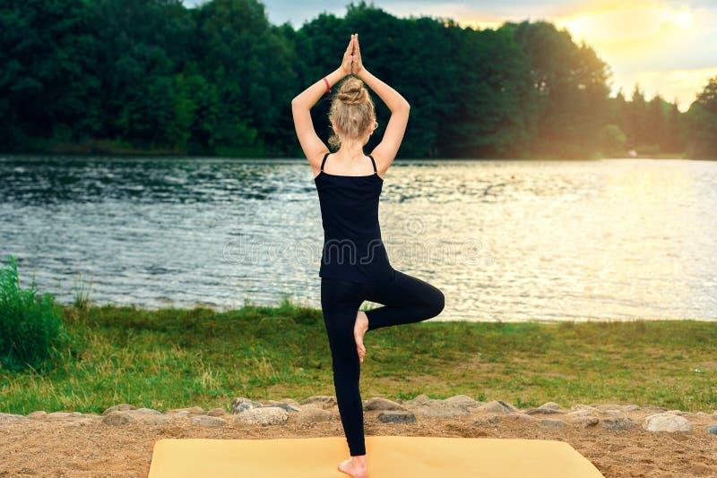 Młoda dziewczyna w czarnych leggings i koszulce siedzi na kamieniu w lotosowej pozie blisko jeziora obraz stock
