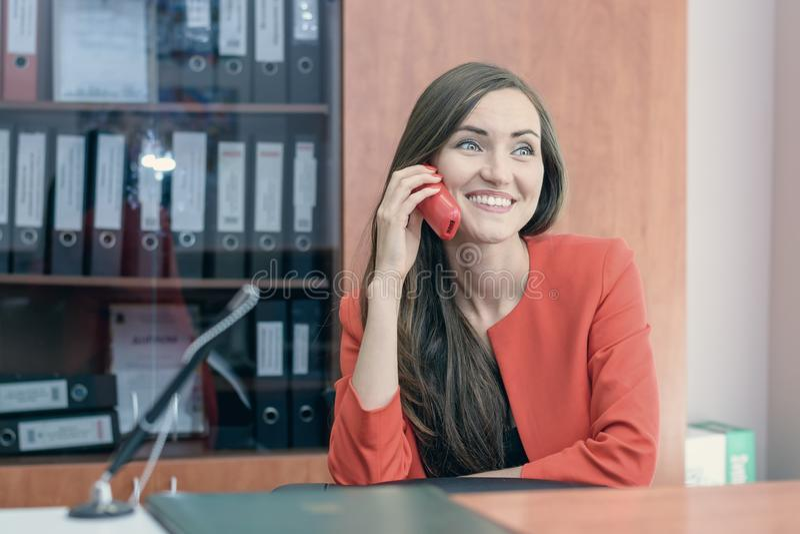 Młoda dziewczyna w czerwonym kostiumu siedzi z powrotem przy pracą, opowiada na telefonie z przyjaciółmi praca biurowa obraz stock