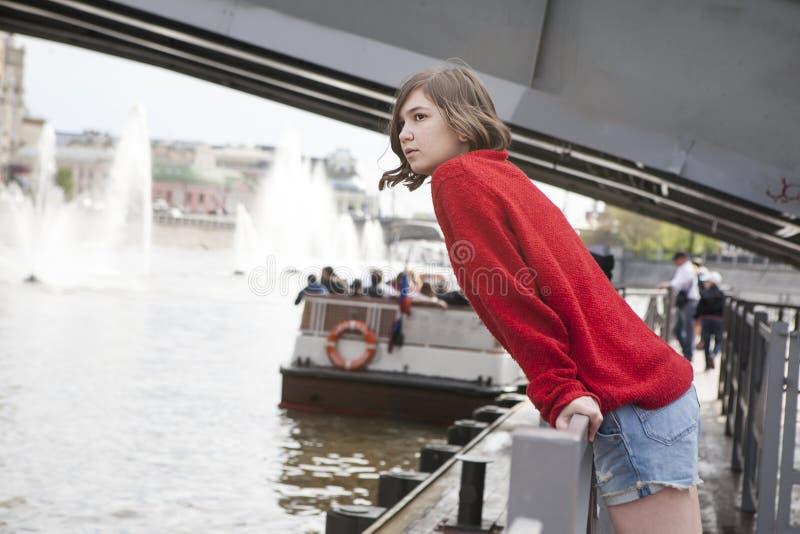 Młoda dziewczyna w czerwonym wełna pulowerze i cajgów skrótach Opierał przeciw poręczowi obok kanału zdjęcia royalty free