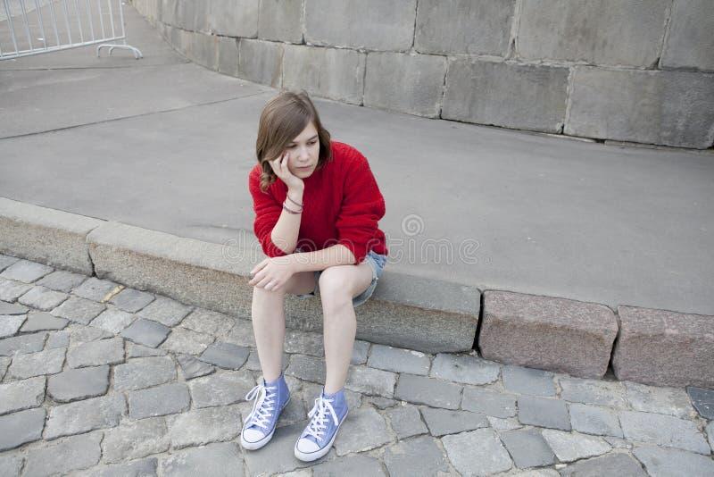 Młoda dziewczyna w czerwonym wełna pulowerze i cajgów skrótach siedzi na krokach obrazy royalty free