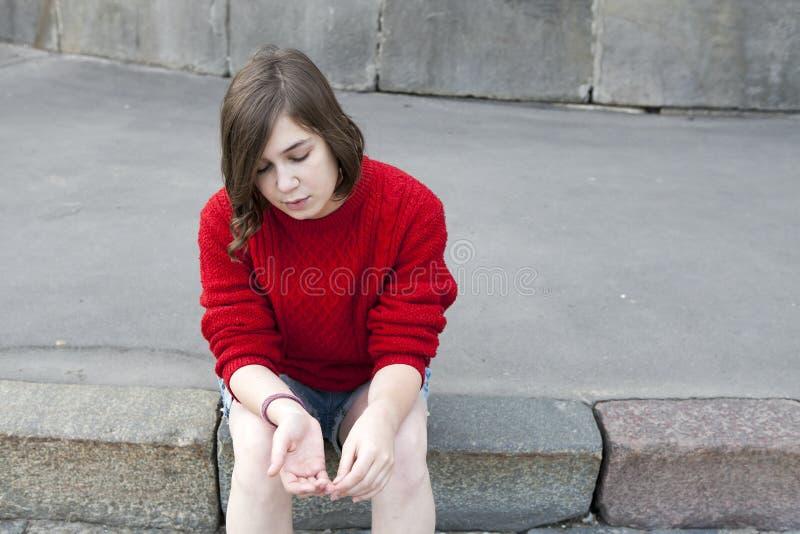 Młoda dziewczyna w czerwonym wełna pulowerze i cajgów skrótach siedzi na krokach fotografia stock