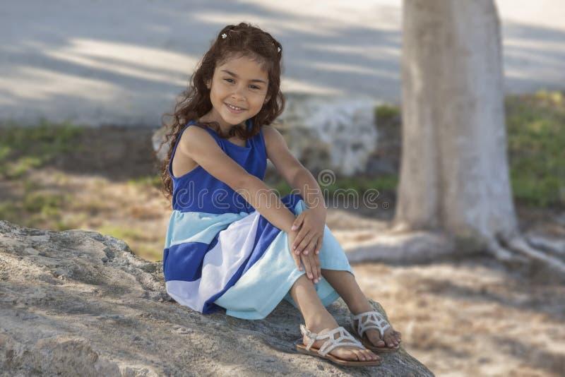 Młoda dziewczyna w długiej sukni siedzi na wielkiej skale pod drzewem w Floryda parku obrazy stock