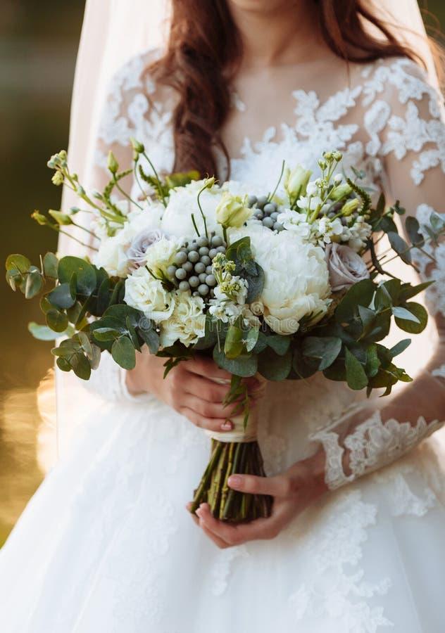 Młoda dziewczyna w eleganckiej sukni jest stojąca i trzymać ręka bukiet pastel kwitnie i zielenieje z faborkiem przy naturą obrazy royalty free