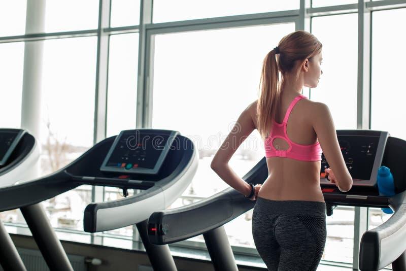 Młoda dziewczyna w gym styl życia zdrowym bieg na kieratowy przyglądającym za nadokiennym główkowanie plecy widoku obrazy royalty free