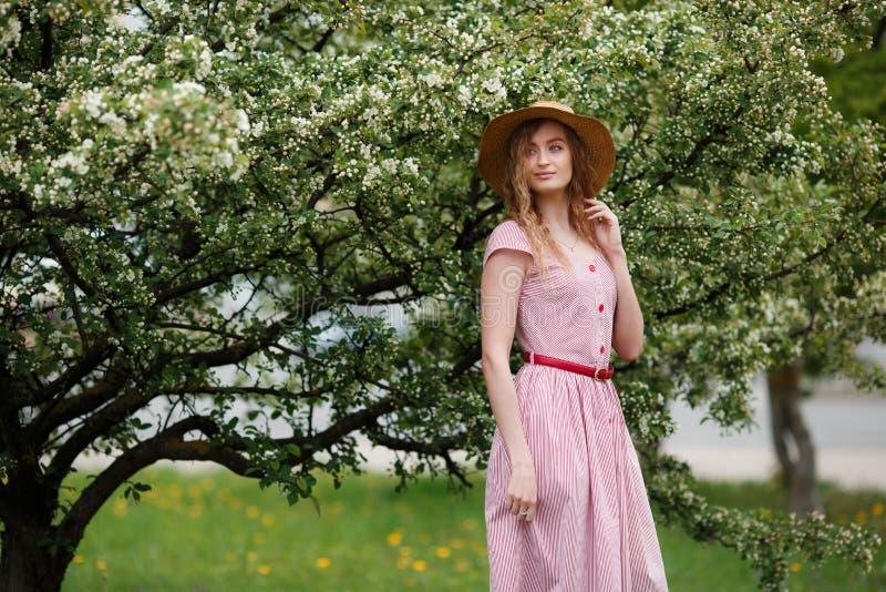 Młoda dziewczyna w kapeluszu blisko kwiatonośnego drzewa w parku ?adny czu?o?? model patrzeje kamer? obraz stock